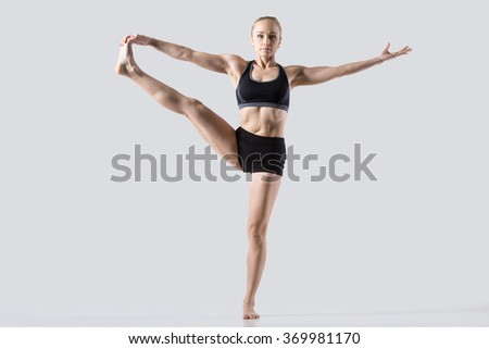 Sporty beautiful young woman practicing yoga, doing Utthita Hasta Padangustasana, Extended Hand to Big Toe pose, working out wearing black sportswear, studio full length, grey background