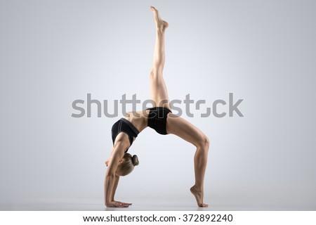 Sporty beautiful young woman practicing yoga, doing variation of Bridge Pose, One-legged Upward Bow (Wheel) Posture, Eka Pada Urdhva Dhanurasana, working out wearing black sportswear, studio - stock photo