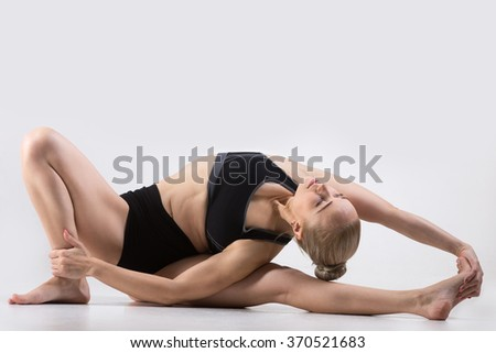 Sporty beautiful young woman practicing yoga, doing variation of Parivrtta Janu Sirsasana, Revolved Head-to-Knee Forward Bend Pose, working out wearing black sportswear, studio