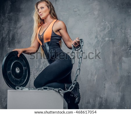 Sporty blond female holding barbell weight and iron chain over grey background.