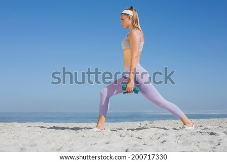 Sporty blonde doing weighted lunges on the beach on a sunny day