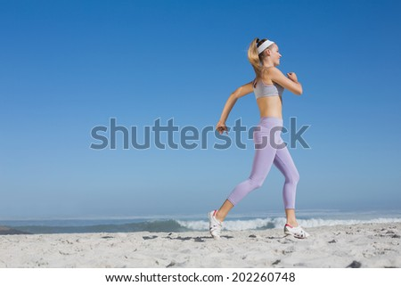 Sporty blonde on the beach jogging on a sunny day - stock photo