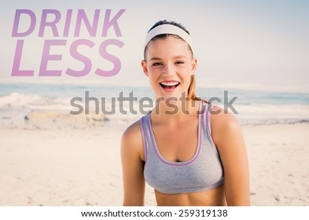 Sporty blonde on the beach smiling at camera against drink less - stock photo