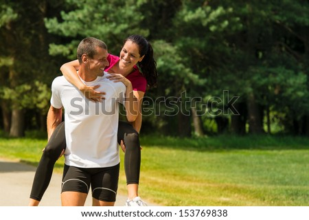 Sporty boyfriend giving piggyback ride to his girlfriend - stock photo