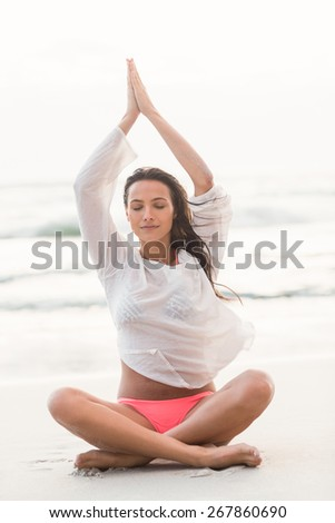 Sporty brunette sitting in lotus pose on the beach - stock photo