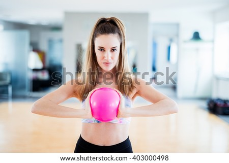 Sporty brunette woman with pigtail training at gym with a ball - stock photo