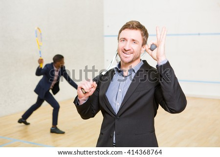 Sporty businessman in business suit smiling for camera and holding ball for squah on court. His business partner playing squash on background. - stock photo