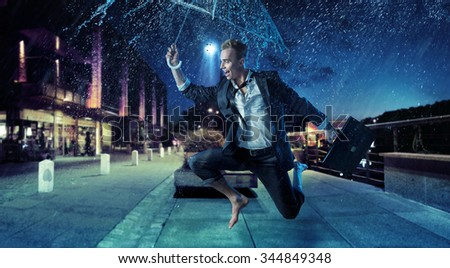 Sporty businessman running with an umbrella - stock photo