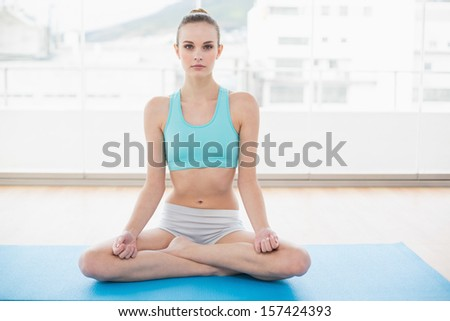 Sporty calm woman sitting cross-legged on exercise mat in bright room
