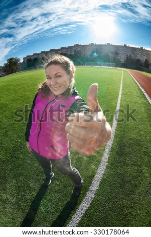 Sporty Caucasian happy woman standing on green playing field, showing thumb up, full length portrait - stock photo