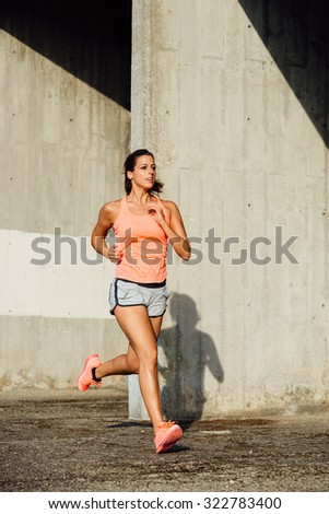 Sporty cheerful woman running and training outdoor. Female runner exercising. - stock photo