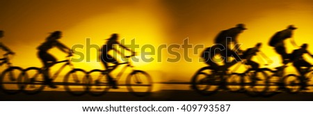 Sporty company friends on bicycles outdoors against sunset Silhouette eight 8 cyclist going along shoreline coast Reflection sun on water Sport in Nature background Group of people. Empty Copy Space