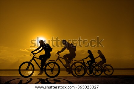 Sporty company friends on bicycles outdoors against sunset Silhouette five 5 cyclist going along shoreline coast Reflection sun on water Sport in Nature background Group of people. Empty Copy Space