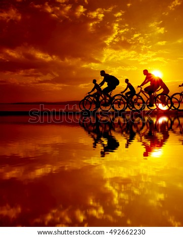Sporty company friends on bicycles outdoors against sunset Silhouette team cyclist going along shoreline coast Reflection sun on water Sport in Nature background Group of people. Empty Copy Space