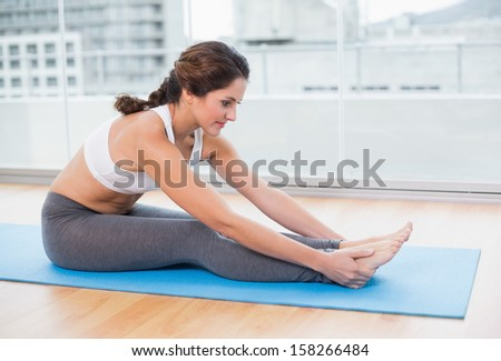 Sporty content brunette stretching in bright room