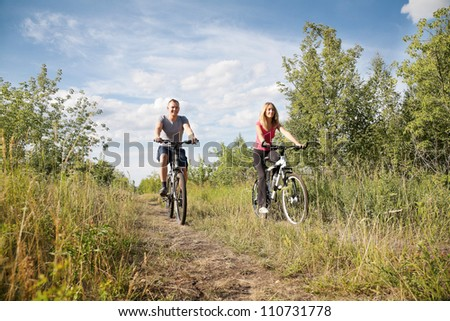 Sporty couple biking in the forest at summer - stock photo