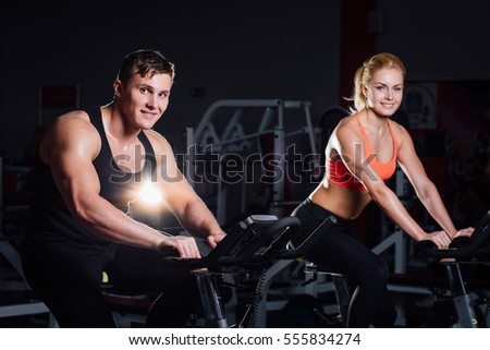 Sporty couple exercising at the fitness the exercise bike on a dark background at gym.