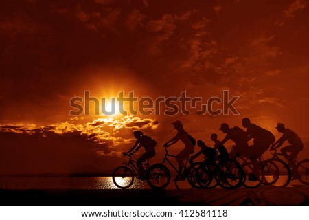 sporty couple friends on bicycles outdoors against sunset. Silhouette of motion go of four 4 cyclist along shoreline coast Reflection sun on water. Empty Copy Space for inscription, people or objects - stock photo