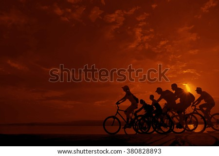 sporty couple friends on bicycles outdoors against sunset. Silhouette of motion go of six 6 cyclist along shoreline coast Reflection sun on water. Empty Copy Space for inscription, people or objects