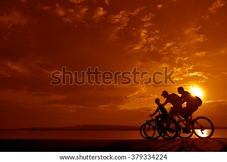 sporty couple friends on bicycles outdoors against sunset. Silhouette of motion go of two 2 cyclist along shoreline coast Reflection sun on water. Empty Copy Space for inscription, people or objects