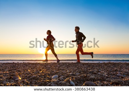 Sporty Couple Man and Woman doing Morning Jogging on Sea Beach at Bright Sunrise Silhouettes - stock photo