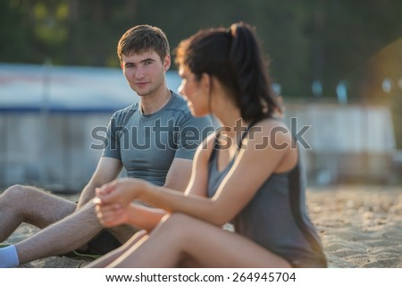 Sporty couple resting after workout on beach during sunset - stock photo