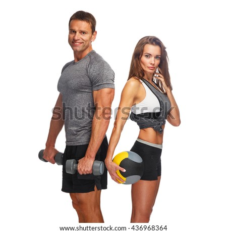 Sporty couple with dumbbells and ball isolated on a white background. - stock photo