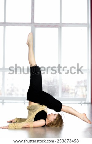 Sporty dancer woman in class working out, doing leg swings in yoga pose Sarvangasana, Shoulderstand - stock photo