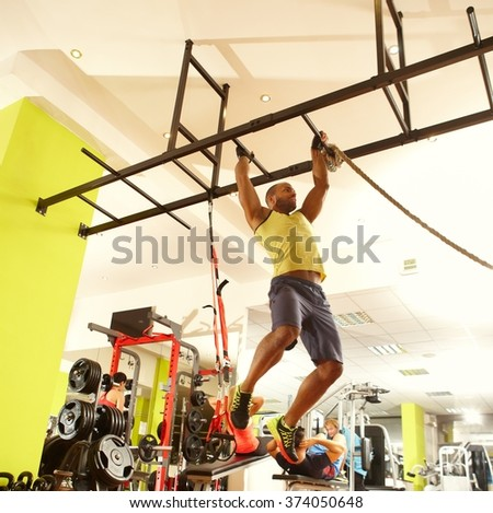 Sporty ethnic man training in fitness club, hanging on. - stock photo
