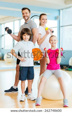 Sporty family. Happy family holding different sports equipment while standing close to each other in health club  - stock photo