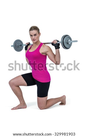 Sporty female bodybuilder lifting barebell against white background