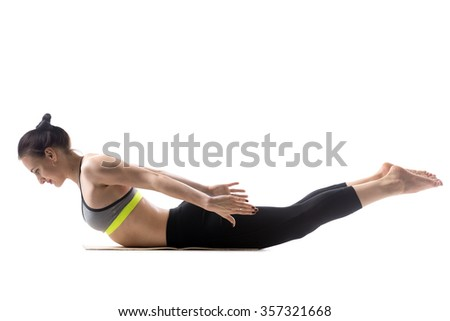 Sporty fit beautiful young brunette woman in sportswear bra and black pants working out, doing Salabhasana, Locust, Grasshopper Pose, Double Leg Kicks, studio full length, isolated, white background - stock photo