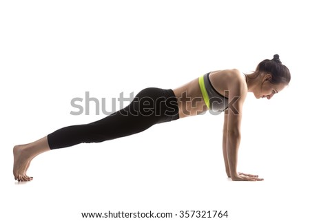 Sporty fit beautiful young brunette woman in sportswear bra and black pants working out, doing push-ups, Phalankasana, Plank Pose for abdominal muscles, studio full length, isolated, white background