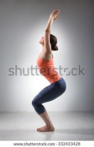 Sporty fit woman doing Surya Namaskar ashtanga vinyasa yoga asana Utkatasana - chair pose - stock photo