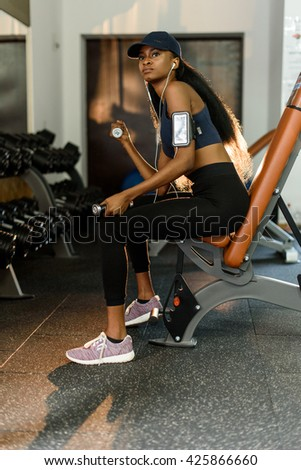 Sporty fitness african american woman working out with dumbbells at the gym and listens music in earphones