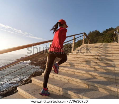 sporty fitness female runner running upstairs on coast trail