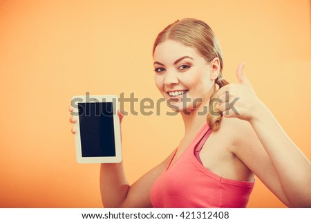 Sporty fitness girl holding tablet computer with blank screen showing copyspace. Happy smiling woman advertising new modern technology giving thumb up gesture. - stock photo