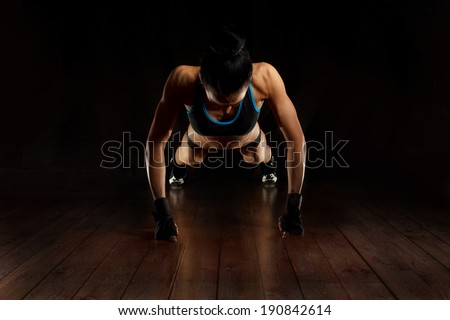 sporty girl doing exercise pushups on wooden floor, silhouette  studio shot  - stock photo