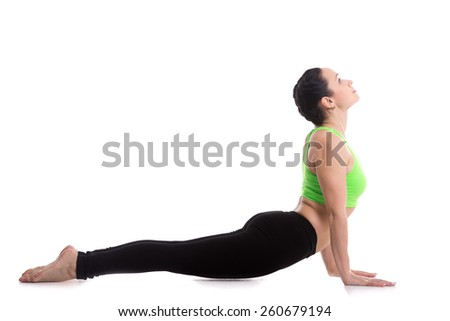 Sporty girl doing exercises for flexible spine on white background, yoga asana from Surya Namaskar sequence, Sun Salutation complex, urdhva mukha shvanasana (upward facing dog pose) - stock photo