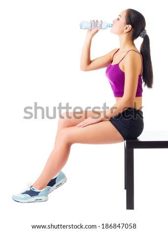 Sporty girl drinks water isolated - stock photo