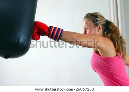 Sporty girl in boxing gloves punching (action shot)