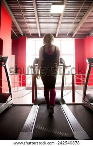 Sporty girl in sportswear walks on cardio trainer, treadmill in gym (view from the back) - stock photo