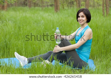 Sporty girl in the wood with bottle of water