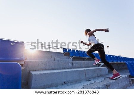 Sporty girl in white shirt running fast to a sunset on a stadium. Side view. Dynamic photo. Young woman in sportswear training on a stadium. Copy space. Sport lifestyle concept - stock photo