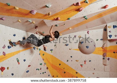 Sporty girl making effort when climbing up the wall - stock photo