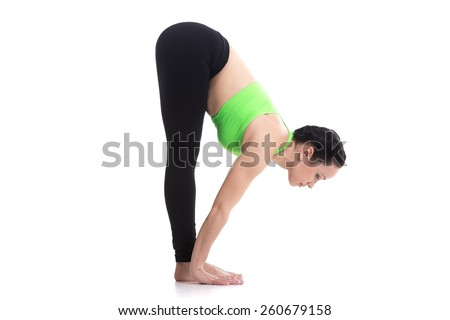 Sporty girl on white background in standing forward bend yoga pose (uttanasana), asana from surya namaskar sequence, sun salutation complex, posture for leg muscles - stock photo