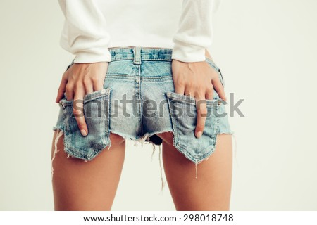 Sporty girl show middle finger, fuck you off sign in back pocket of her mini denim shorts in front of a white wall. Outdoor funny lifestyle portrait, concept of brutal, rebel, punk, furious, indecent - stock photo