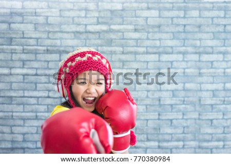 Sporty girl wearing red boxing gloves,she is playing music using a smartphone and wearing red headphones