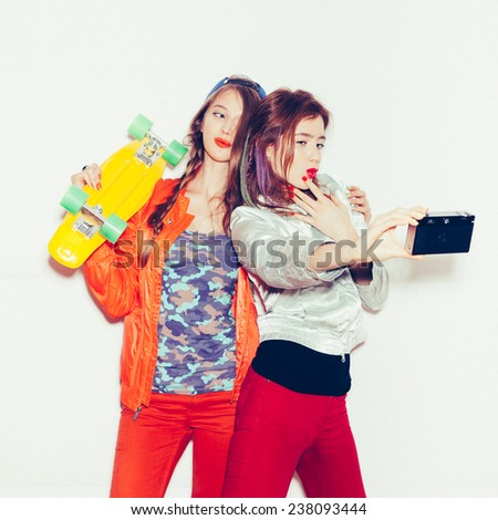 Sporty girlfriends standing having fun together. Beautiful women making selfie. Emotion. Toned.  White background, not isolated - stock photo