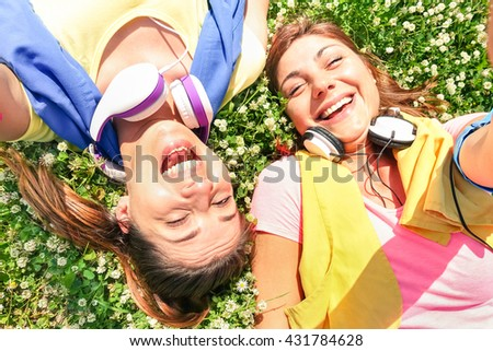 Sporty girlfriends taking selfie break at run training in park area - Happy fitness and fun sport concept with joyful young women - Warm sunny afternoon color tones - Framed hands holding smartphone - stock photo
